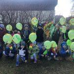 Grupa dzieci pozujących do zdjęcia w ogrodzie przedszkolnym i trzymających w rękach zielone ozdobione balony.