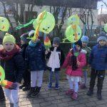 Grupa dzieci idąca na spacer i trzymająca w rękach zielone, ozdobione balony.