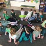 Grupa dzieci siedzących w kole na dywanie, pokazujących założone różne i kolorowe skarpetki