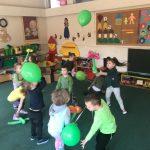 Grupa dzieci bawiacych się w rozsypce, w sali przedszkolnej balonami