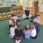 Grupa dzieci siedzącyc0h w sali przedszkolnej na dywanie w kole wraz z Panią.