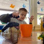 Chłopiec siedzący przy stoliku i sypiacy do pomarańczowej doniczki ziemię.