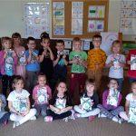 Grupa dzieci pozujących do zdjęcia w dwóch rzędach. Wszystkie dzieci trzymają w rękach upominki.