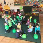 Grupa dzieci bawiących się balonami w sali przedszkolnej.