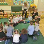 Grupa dzieci siedzących w sali przedszkolnej na dywanie w kole wraz z Panią. Z tyłu koła stoi pochylona nad dziećmi druga Pani.