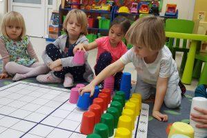 Czworo dzieci siedzących na dywanie w sali przedszkolnej. Przed dziećmi znajduje się mata z kolorowymi kubkami. Chłopiec trzyma w ręku niebieski kubek, który układa na matę. Dziewczynka trzyma w ręku różowy kubek.