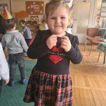 Dziewczynka pozująca do zdjęcia w sali przedszkolnej, na stojąco. W tle widać stojące dzieci i Panią.