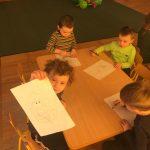 Czworo dzieci siedzących przy stoliku i kolorujących kolorowanki.