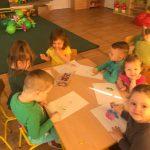 Sześcioro dzieci siedzących przy stoliku i kolorujących kolorowanki.