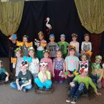 Gruoa dzieci pozujących do zdjęcia w sali przedszkolnej i mających założone na głowach kolorowe, wiosenne opaski. Trzech chłopców siedzi w gnieździe bociana. W tle widoczna wiosenna dekoracja.