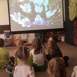 Siedmioro dzieci siedzących na dywanie i oglądających na ekranie kwiaty.