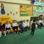 Grupa dzieci siedząca w sali przedszkolnej, w rzędzie na krzesłach. Dwóch chłopców stoi przed dziećmi.