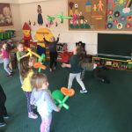 Grupa dzieci bawiacych się w rozsypce, w sali przedszkolnej kolorowymi balonami
