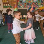 Dzieci trzymające się za ręce i tańczące w parach kółeczku. Na drugim planie, z lewej strony chłopiec stoi sam. Wszystkie dzieci mają na głowach założone kolorowe czapeczki.