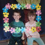 Dziewczynka i chłopiec pozujacy do zdjęcia w ramce ozdobionej papierowymi kwiatkami.
