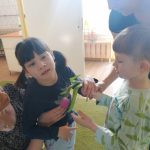 Chłopiec wraz z Panią wręczający dziewczynce, którą trzyma Pani tulipana.