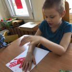 Chłopiec siedzący przy stoliku, odbijający pomalowaną czerwoną farbą dłoń na kartce papieru.