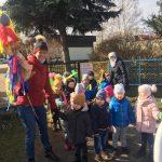 Grupa dzieci idących z dwoma paniami na spacer. Pani stojąca z przodu trzyma w ręku kukę - Marzannę. Dzieci stojace z tyłu trzymaja w rękach balony.