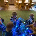 5 dzieci siedzi na dywanie. W środku są położone światłowody, które dzieci trzymają w rękach.