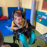 Chłopiec siedzi na specjalistycznym krzesełku. W dłoni trzyma grzechotkę.