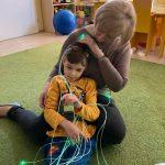 Chłopiec siedzi na dywanie, bawi się światłowodami.Za nim siedzi Pani,. która go podtrzymuje.