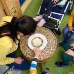 Na stoliku, na talerzu rozłożone są kolorowe cukierki. Wokół stolika siedzą dzieci.