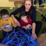 Dziewczynka i chłopiec siedzą na dywanie. Za dwieczyną siedzi Pani, która podtrzymuje dziecko. Przed nimi leżą światłowody.
