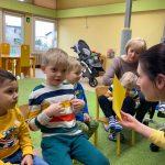 Dzieci siedzą na krzesełkach. Nauczycielka pokazuje żółtą kartkę, a dziecko wskazuje ten kolor na swojej bluzce.