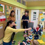3 nauczycielki stoją przed dziećmi, które siedzą na krzesełkach i wózkach. 2 Panie leją dzieci wodą, a jedna posypuje dziecko papierowymi kroplami deszczu