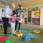 Dziewczynka trzymana przez 2 Panie idzie po dyskach z kolcami. Przed nią leżą 3 worki na śmieci w różnych kolorach.