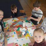 Grupa dzieci siedzi przy stoliku. Przed nimi leżą kartki z wykonaną pracą plastyczną, klej w słoiczku, kolorowe karteczki.