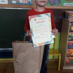 Chłopiec stoi trzymając w rękach dyplom i papierową torbę z podarunkiem.