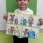 Uśmiechnięty chłopiec stoi trzymając z rękach rysunek z misiami.