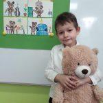 chłopiec stoi trzymając w rękach dużego, pluszowego misia. Po jego prawej stronie na tablicy powieszony jest rysunek z misiami