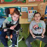 2 chłopców siedzi na krześle. Na bluzce mają przyczepione medale.