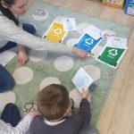 Chłopiec siedzi z Panią na dywanie. Przed nimi leżą 3 obrazki z kolorowymi koszami na śmieci.
