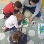 3 dzieci siedzi na dywanie razem z Panią. Dziewczynka układa rozcięty obrazek Ziemi.