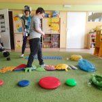 Chłopiec idzie po dyskach z kolcami leżącymi na ziemi. Przed nim leżą 3 worki na śmieci w różnych kolorach.