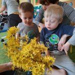 2 chłopców razem z Panią siedzą na krześle. Patrzą na bukiet kwiatów.