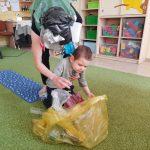 Chłopiec trzymany przez Pania przebrana w strój zanieczyszczonej ziemi wrzuca śmieci do worka.