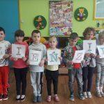 Grupa dzieci stoi z rzędzie. Każde dziecko trzyma kartkę z różną literą. Powstał napis : Dzień Ziemi.