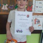 Chłopiec trzyma w ręce dyplom, a w drugiej paczkę z upominkiem.