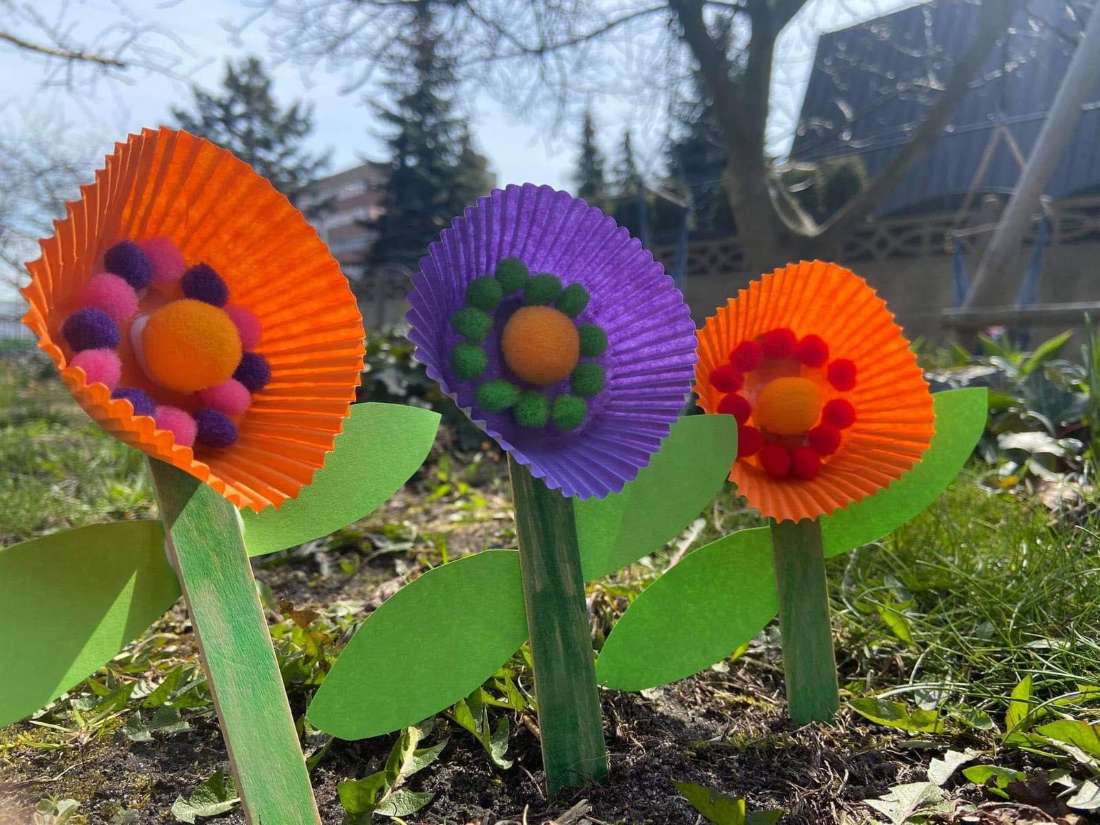 trzy papierowe kwiatki na tle drzew.