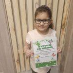 Dziewczynka w okularach stoi z dyplomem w rękach