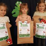 3 dziewczynki stoją trzymając w rękach dyplomy i paczki papierowe z biedronką.