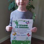 Dziewczynka stoi z dyplomem w rękach