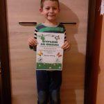 Chłopiec stoi z dyplomem w rękach.