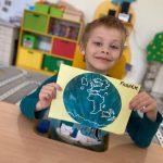 Chłopiec siedzący przy stoliku i trzymajacy w ręku pracę plastyczna - planetę Ziemię.
