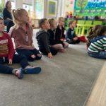 Grupa dzieci siedzących w dwóch rzędach na dywanie. Za dziećmi, na krzesełku siedzi Pani.