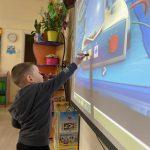 Chłopiec trzymający w ręku interaktywny pisak i wykonujący zadanie na tablicy multimedialnej
